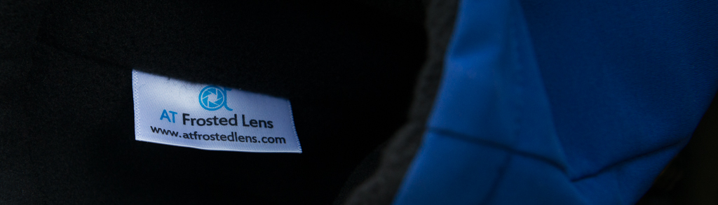 Label inside a camera parka with AT Frosted Lens logo and website info.
