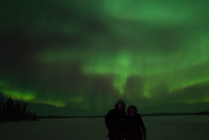 The two owners of AT Frosted Lens under the northern lights in Yellowknife, NWT, Canada